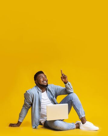Great offer. Black millennial guy sitting on floor with laptop and pointing upwards at copy space on yellow