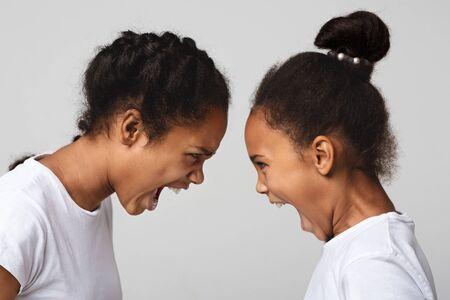 Generation conflict. Furious black sisters quarreling, grey studio Imagens