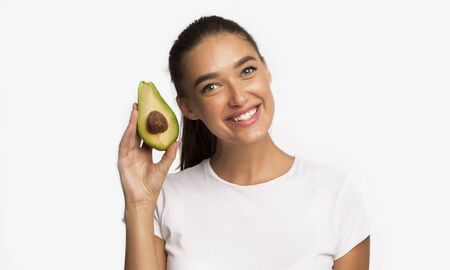 Healthy Fats. Smiling Woman Holding Avocado Standing Over White