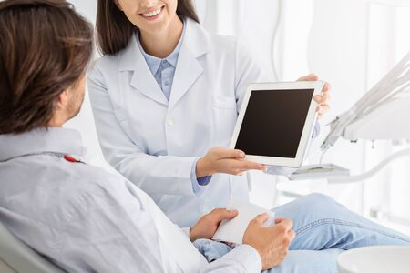Cropped image of female dentist showing patient empty digital tablet screen, modern technologies in stomatology, copy space