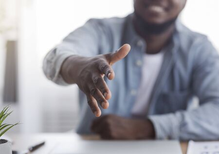 Youre hired. Smiling black HR manager extending hand for handshake after successful job interview, selective focus on arm.