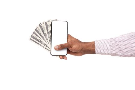 Profitable investment. Smartphone with blank screen and cash in black male hand over white background, copy space Stok Fotoğraf