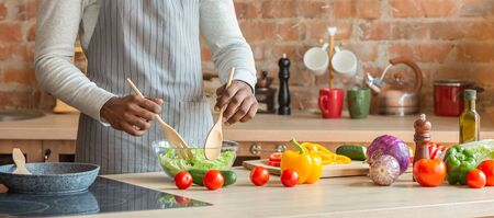 Man in kitchen. Hands of black man preparing fresh healthy salad at kitchen, cropped, panorama with copy space