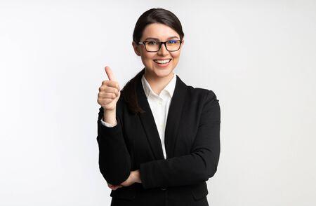 Igual que. Empresaria sonriente que gesticula los pulgares para arriba que se colocan sobre el fondo blanco. Tiro del estudio