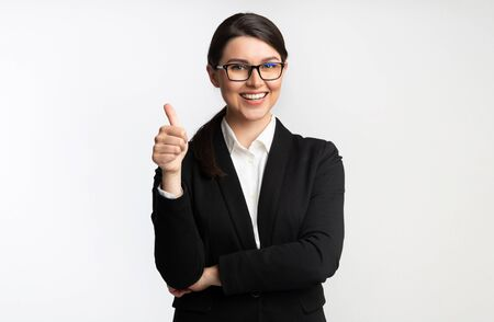 Like. Smiling Businesswoman Gesturing Thumbs Up Standing Over White Background. Studio Shot