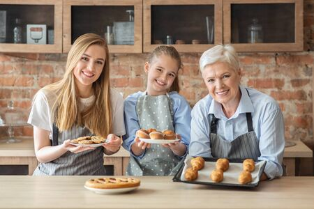 Happy female family showing freshly baked home pastry, granny, mom and daughter cooking at kitchen together Zdjęcie Seryjne