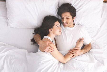 Joven pareja amorosa durmiendo en la cama por la mañana y abrazos, concepto de amor y relaciones, vista superior