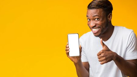 Cool App. Afro Man Showing Smartphone With Blank Screen Gesturing Thumbs Up Standing On Yellow Background. Mockup, Panorama, Copy Space