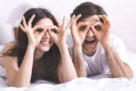 Cheerful couple in love having fun in bed, holding fingers near eyes like glasses