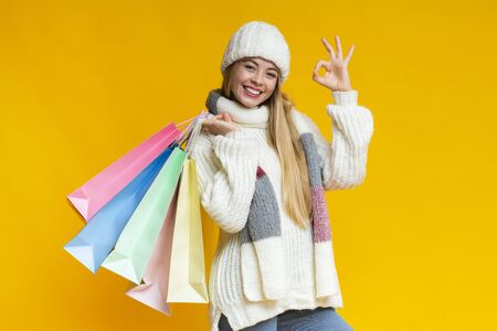 Beautiful smiling girl in warm clothes showing okay sign, holding shopping bags, yellow background