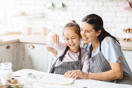 Pretty little girl and her attractive mom making cookies together, having fun in kitchen.