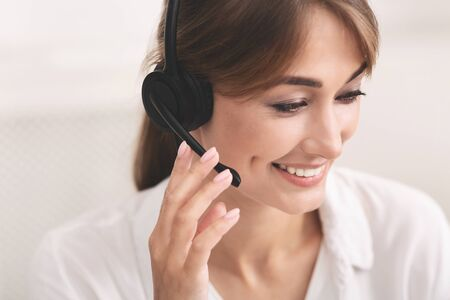 Call Center Hotline. Smiling Girl In Headset Receiving Customers Feedback On Phone Over White Background