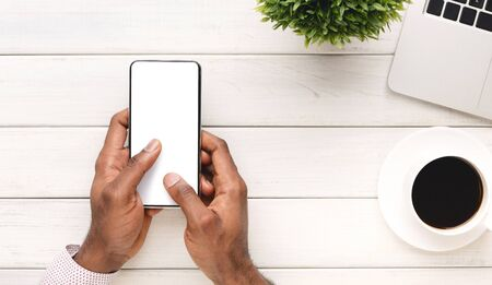 Cool app. Black mans hands holding modern smart phone with blank screen at workplace, top view