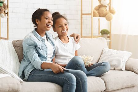 Two cheerful black girls enjoying movie, eating popcorn at home, empty space