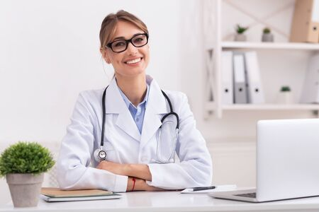 Family Medical Doctor. Positive Woman Physician Smiling Looking At Camera Sitting In Her Office. Foto de archivo - 131495755