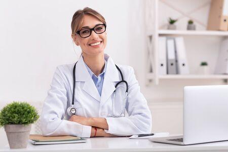 Hausarzt. Positiver Frauenarzt, der die Kamera betrachtet, die in ihrem Büro sitzt.