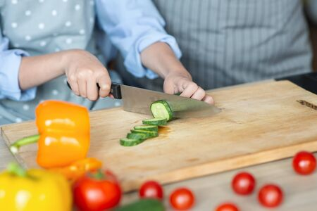Child learning how to cut veggies, helping adults with dinner, close up Stock Photo