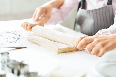 Homemade cooking. Small girl rolling out dough on kitchen table with help of her mom, closeup