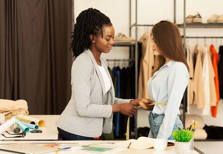 Couture. Dame de tailleur afro-américaine mesurant la taille de la femme travaillant dans l'atelier de vêtements. Banque d'images