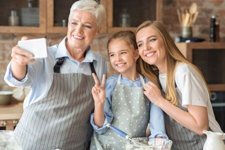 Friendly female family making selfie using smartphone at kitchen, cropped