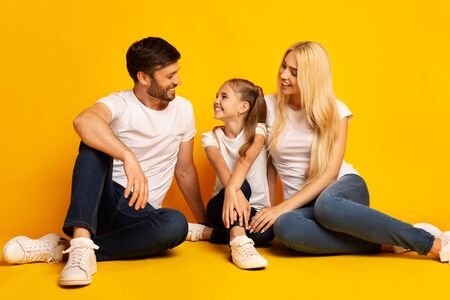Loving Family Talking Sitting On Floor Spending Time Together Over Yellow Background. Studio Shot Stock Photo