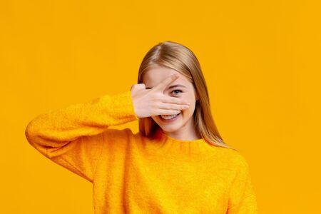 Playful teen girl covering face with hand and peeking through fingers over orange background with copy space