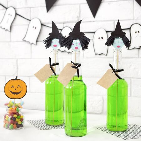 Cute halloween witches ready for party over white bricks wall background