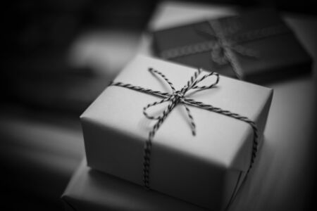Lost gift. Black and white Christmas presents on table, blurred background