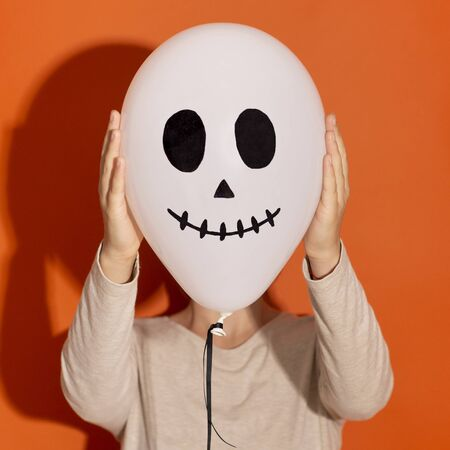 Halloween costume party. Close up of ghost balloon hiding woman face on orange background
