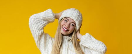 Portrait of joyful pretty young woman in woollen hat, yellow studio background, panorama with copy space