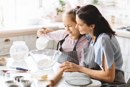 Happy mother and daughter preparing dough together, adding milk to a bowl.