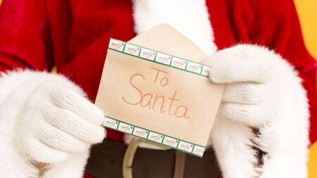 Merry Christmas. Santa Claus holding wish letter with text in hands over yellow background