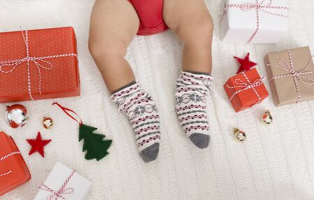 Christmas holidays. Little baby legs in winter socks with Xmas gifts, top view