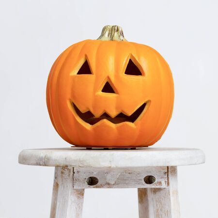 Happy halloween holidays. Close up of pumpkin head on chair over white background