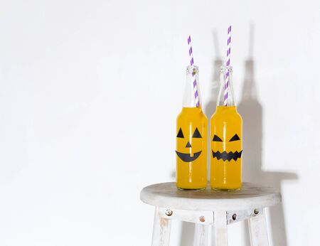 Creative Halloween cocktails in glass bottles with straw preparing for party, white background