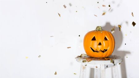 Celebrating Halloween. Pumpkin on background with flying gold confetti and copy space for greetings, panorama