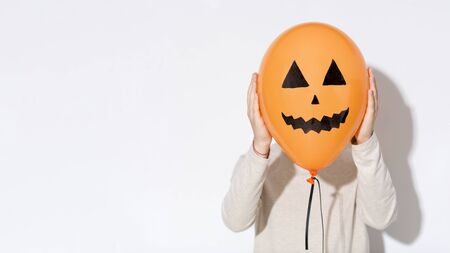 Fooling. Woman hiding her face behind funny Halloween balloon on white background, panorama, copy space