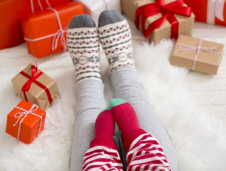 Xmas family background. Legs of baby and mom in winter socks, sitting on floor with Christmas gifts, free space