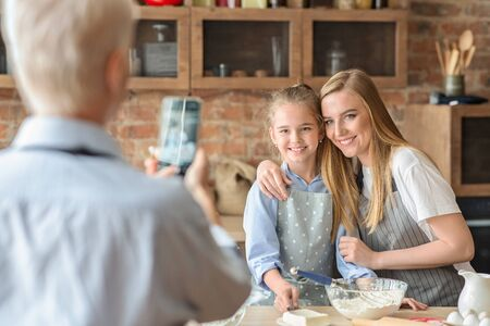 Granny taking photo of her happy daughter and granddaughter cooking in kitchen