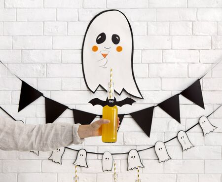 Healthy Halloween party. Woman holding glass bottle with pumpkin punch on background with ghost decoration