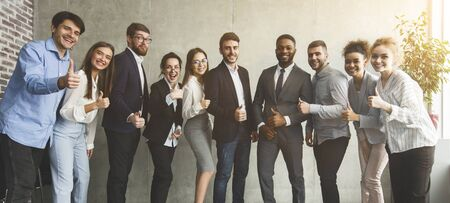 Happy diverse business team showing thumbs up during break in office, panorama