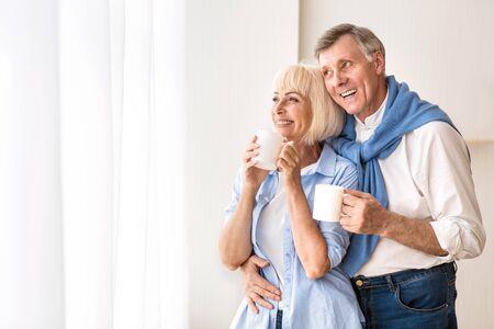 Enjoying coffee time. Loving senior couple standing near window and drinking tea, free space