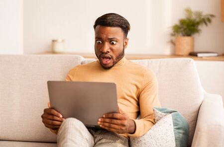 Schockierter schwarzer Kerl, der Laptop-Computer betrachtet, die zu Hause auf der Couch sitzt. Selektiver Fokus