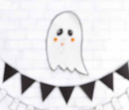 Blurred Halloween cute ghost flying above decorations and drinking cocktail