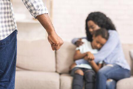 Violencia doméstica. Madre e hija que sufren abusos en el hogar, madre que protege al niño del puño del padre. Foto de archivo