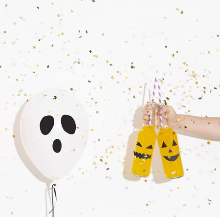 Halloween creative card. Party confetti flying down on balloon and drinks in bottles, white background