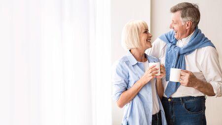 Happy senior couple talking near window and drinking tea, copy space