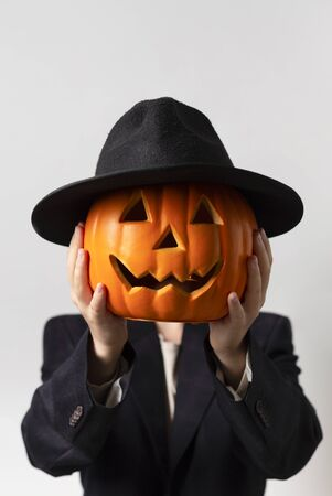 Halloween man with pumpkin head in Jack o Lantern costume over gray background, vertical panorama