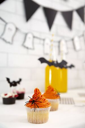 Trick or treat. Orange cup cakes and Halloween drinks on table, bricks wall with decorations, vertical panorama