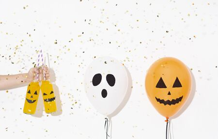 Happy Halloween party with yellow cocktails and balloons with scary faces, white background